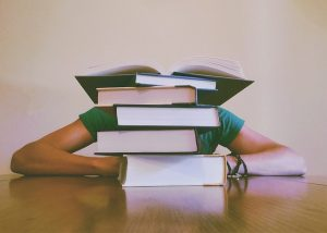 Person hiding behind a pile of books